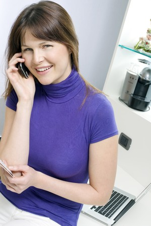 portrait of a young caucasian woman with mobile holding health card and booking medical exam photo