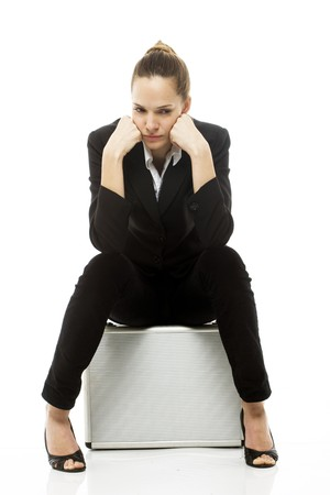 Young businesswoman sitting on a briefcase on white background studio photo