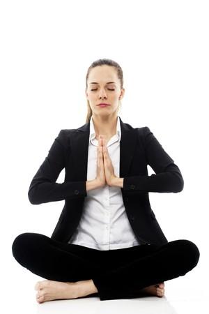 Young businesswoman doing yoga on white background studio photo