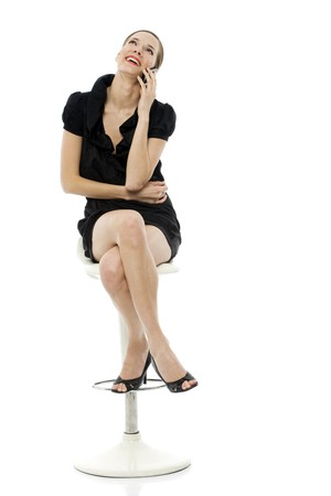 cross leg: inteligente mujer sentada en un taburete de celebraci�n de un m�vil sobre fondo blanco