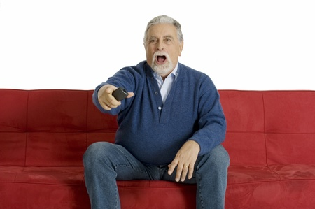 old man on the sofa with television remote control photo