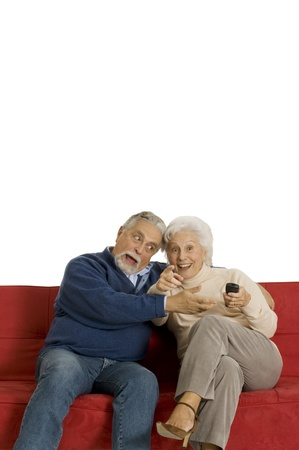 elderly couple on the sofa with television remote control photo