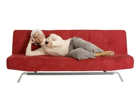 elderly woman on the sofa with television remote control photo