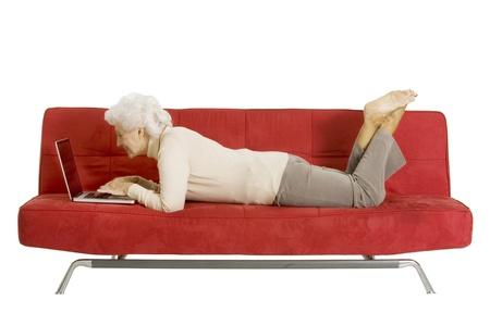 senior ordinateur: femme �g�e sur le canap� avec ordinateur portable