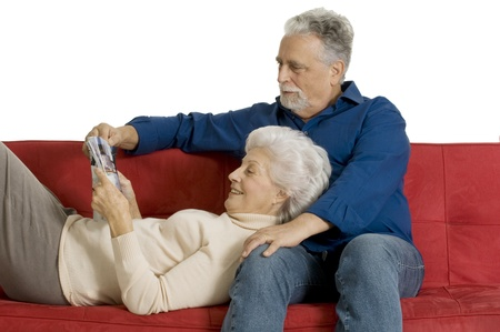 elderly couple on the couch reading a magazine photo