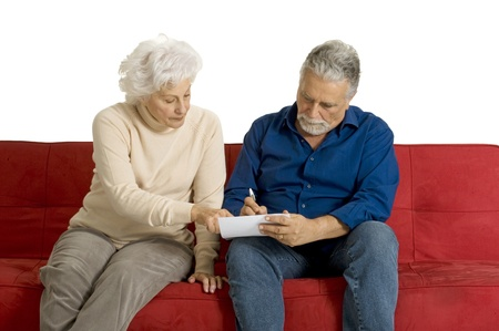 elderly couple on the couch writing photo