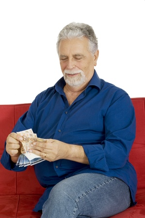 elderly man on the couch with money in hand photo