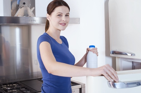 woman opening the refrigerator with milk bottle photo