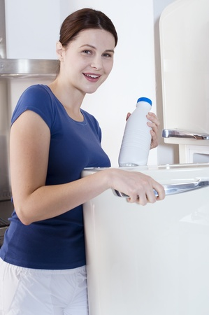 woman taking a bottle of milk from the fridge photo