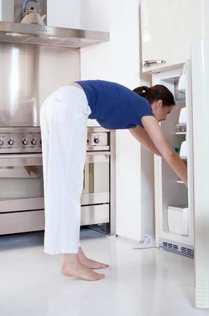 refrigerator: woman opening the refrigerator