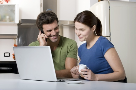 couple in the kitchen with laptop photo