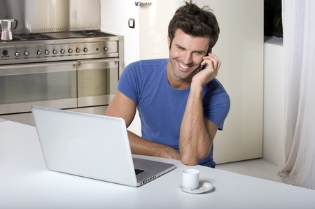 man in the kitchen with laptop and mobile photo