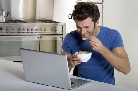 man in the kitchen with laptop having breakfast