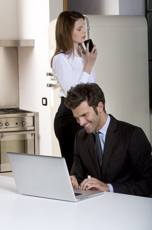 couple at home  with laptop and mobile photo