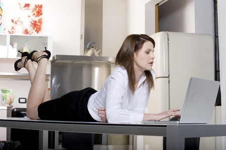 woman in the kitchen on the table with laptop