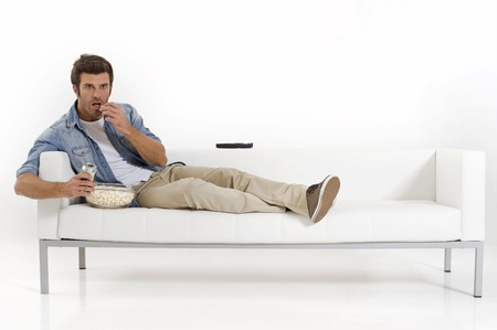only young men: single man on the couch watching TV Stock Photo