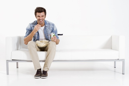 watching tv: single man on the couch watching TV Stock Photo