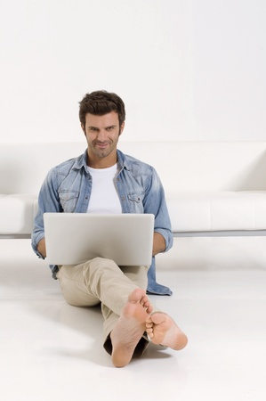 sat: man sitting on the floor with laptop