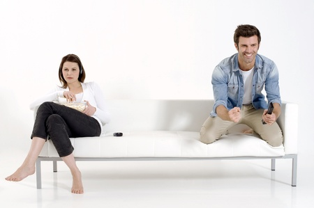 sitted: separated couple on the couch watching TV