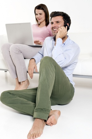woman with laptop and man with mobile