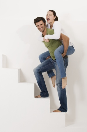 man carrying woman: man climbing the stairs with woman on his shoulders