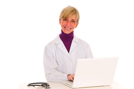 female doctor at the desk with stethoscope and laptop photo