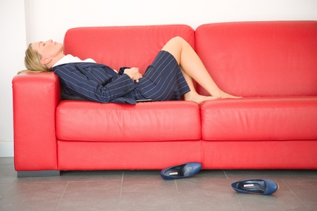 skirt suit: exhausted businesswoman lying on the couch Stock Photo