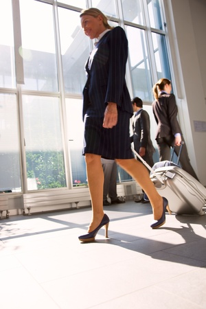 businessman and two businesswoman with trolley photo
