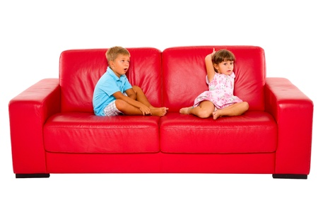 brother and sister on red sofa photo