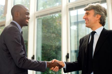 porgere: uomini d'affari si stringono la mano