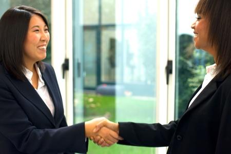 asian american: businesswomen shaking hands