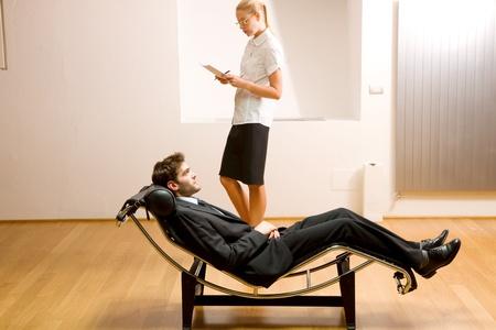 woman reading man lying on chaise longue photo
