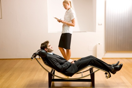 woman reading man lying on chaise longue photo