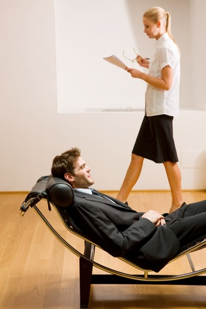 woman reading man lying on chaise longue