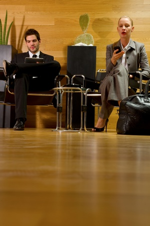 tailleur: business man and business woman waiting in office lobby