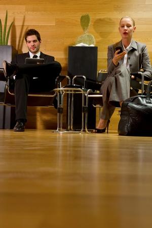 file d attente: homme d'affaires et femme d'affaires en attente dans le hall de bureau Banque d'images