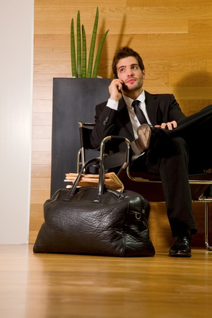 man in chair: business man waiting in office lobby