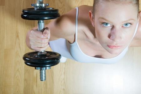 mujer de levantamiento pesas en el gimnasio