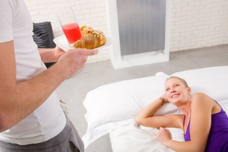 woman lying on the bed man serving breakfast photo