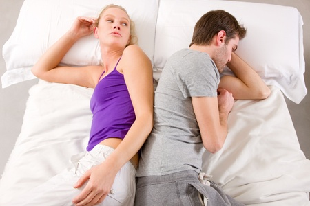 lovers quarrel: couple lying in bed back-to-back having lovers quarrel