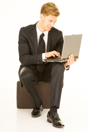 businessman with laptop sitting on a suitcase photo