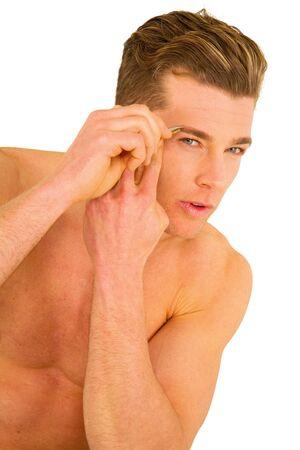 tweezing: young man tweezing eyebrows Stock Photo