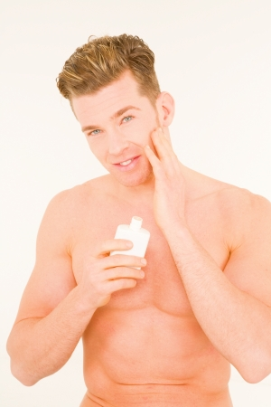 aftershave: Young man applying aftershave