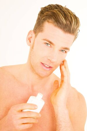 Young man applying aftershave photo
