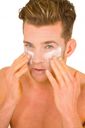 Young man applying lotion on her face photo