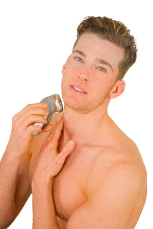 electric razor: Young man shaves with electric razor
