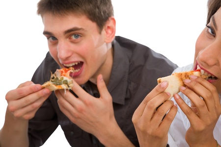 couple of teenagers eating pizza photo