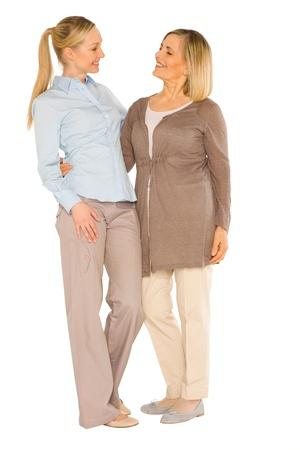 damas antiguas: sonriente abuela y madre joven de pie en el fondo blanco