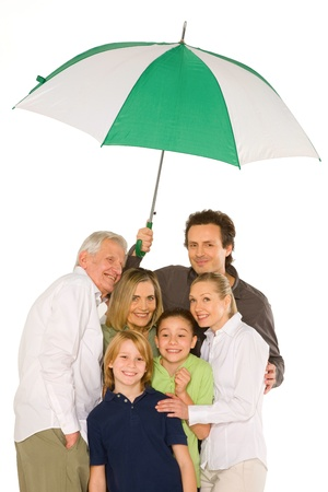 accomplices: three generations family standing isolated on white background holding umbrella