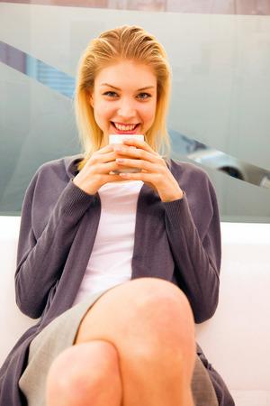 tomando refresco: Mujer joven sonriente que sostiene la taza